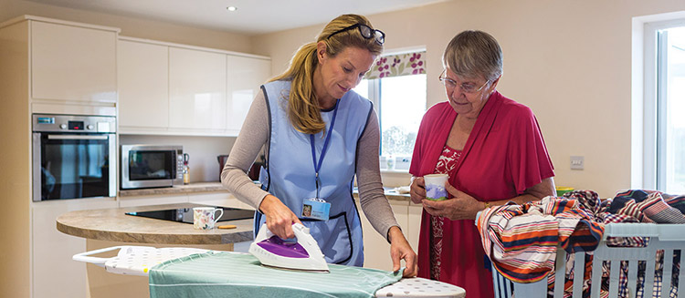 A caregiver is helping an old lady with house chores